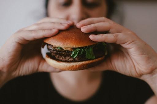 vrouw eet hamburger - overgewicht aanpakken en negatieve voedingspatronen doorbreken met voedingsopstellingen coaching door Greetje De Reys